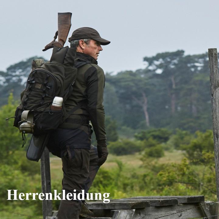 Jäger mit Rucksack und Waffe klettert über einen Zaun
