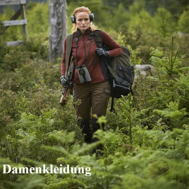 Jägerin mit Fleecejacke, Rucksack und Waffe auf dem Weg zum Ansitz