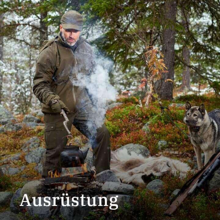 Jäger mit Hund am Lagerfeuer und Teekanne in Schweden