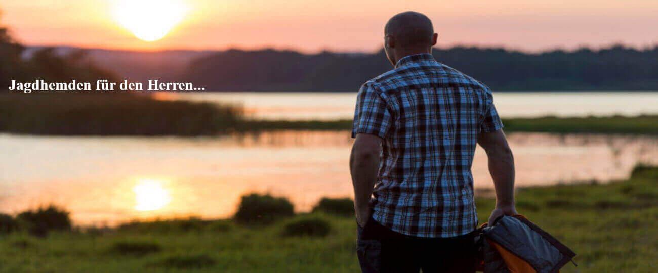 Mann mit kariertem Hemd auf einer Wiese im Sonnenuntergang